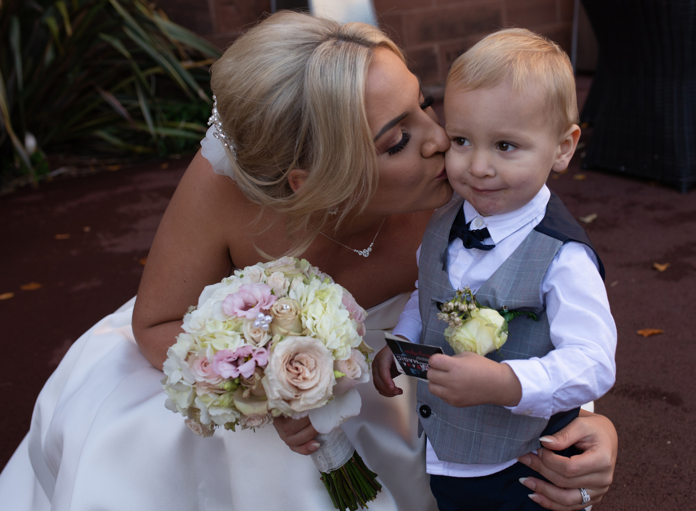 The bride giving her little boy a kiss