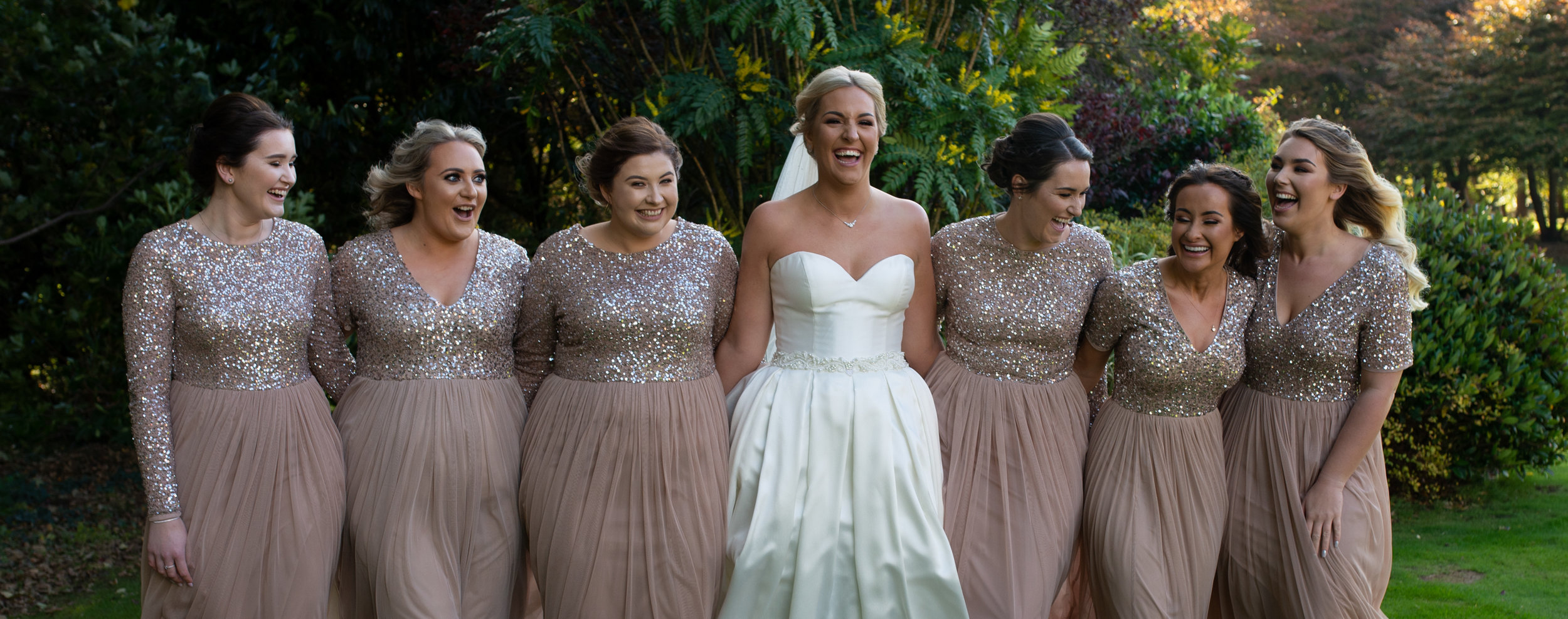 The bride and her bridesmaids having a really good laugh during family group shots