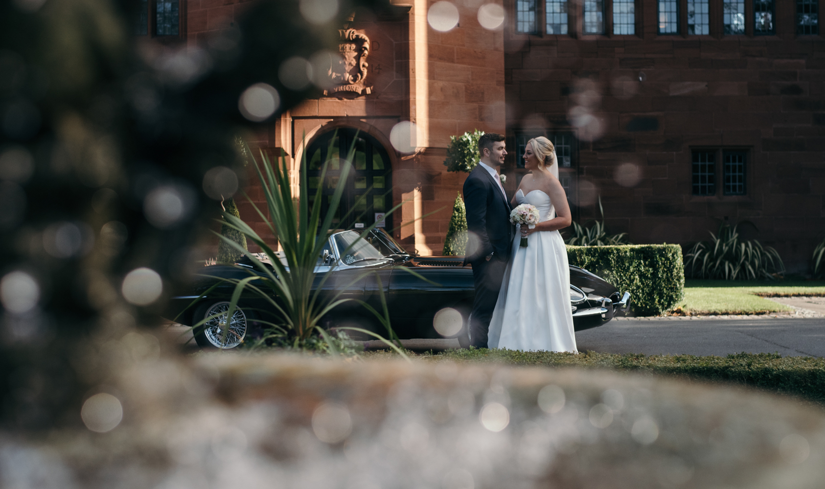 The bride and groom outside Abbey House Hotel standing by the classic e-type jaguar