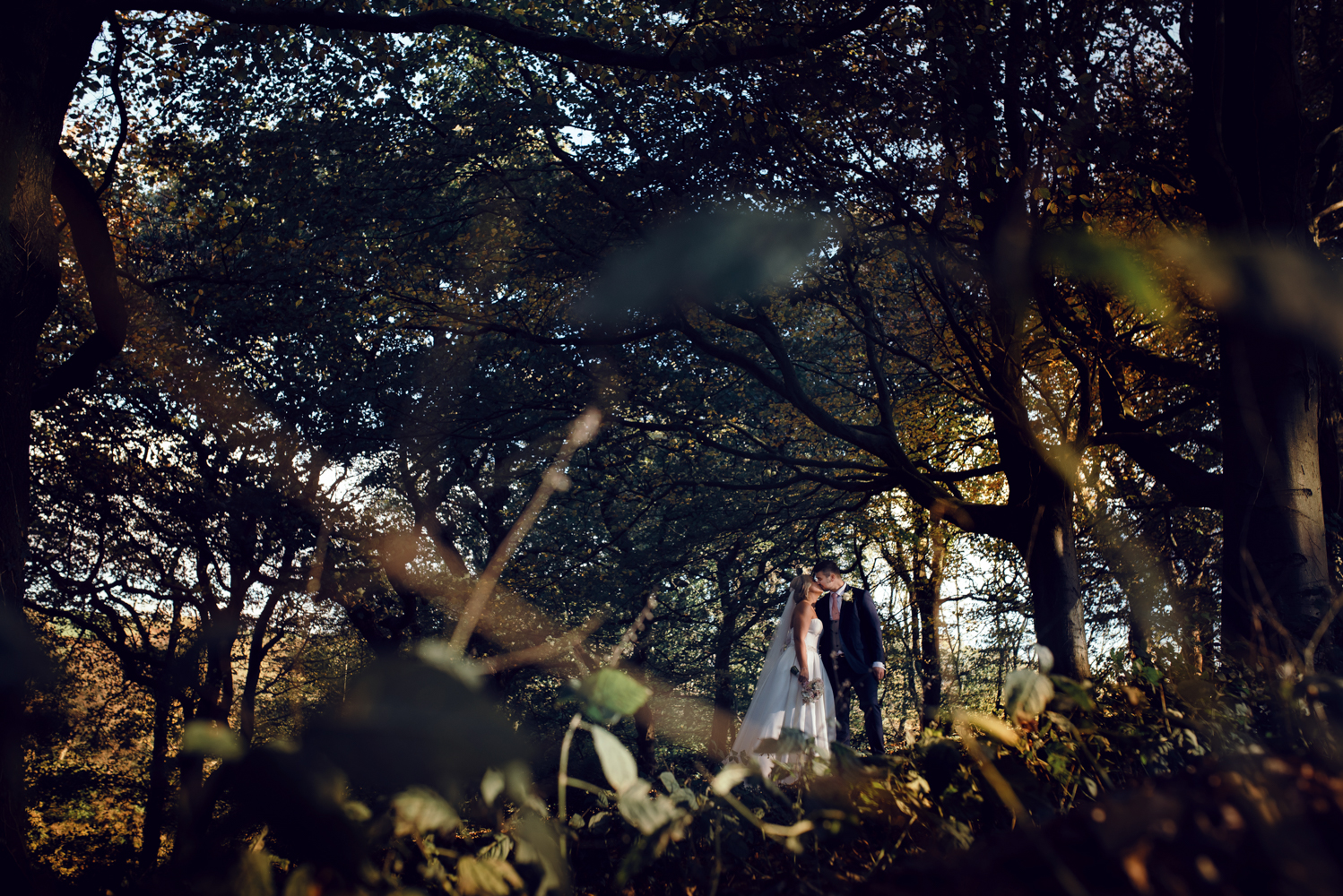 The bride and groom in the woods during the couples portrait session