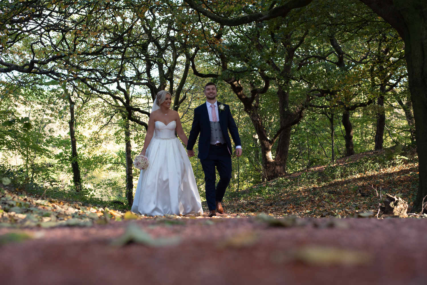 The bride and groom take a walk through the woods at Abbey House Hotel during the couple portrait shoot
