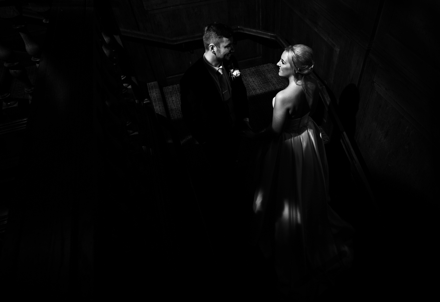 Black and white image of the happy couple taken on the stairs inside the hotel in the dark