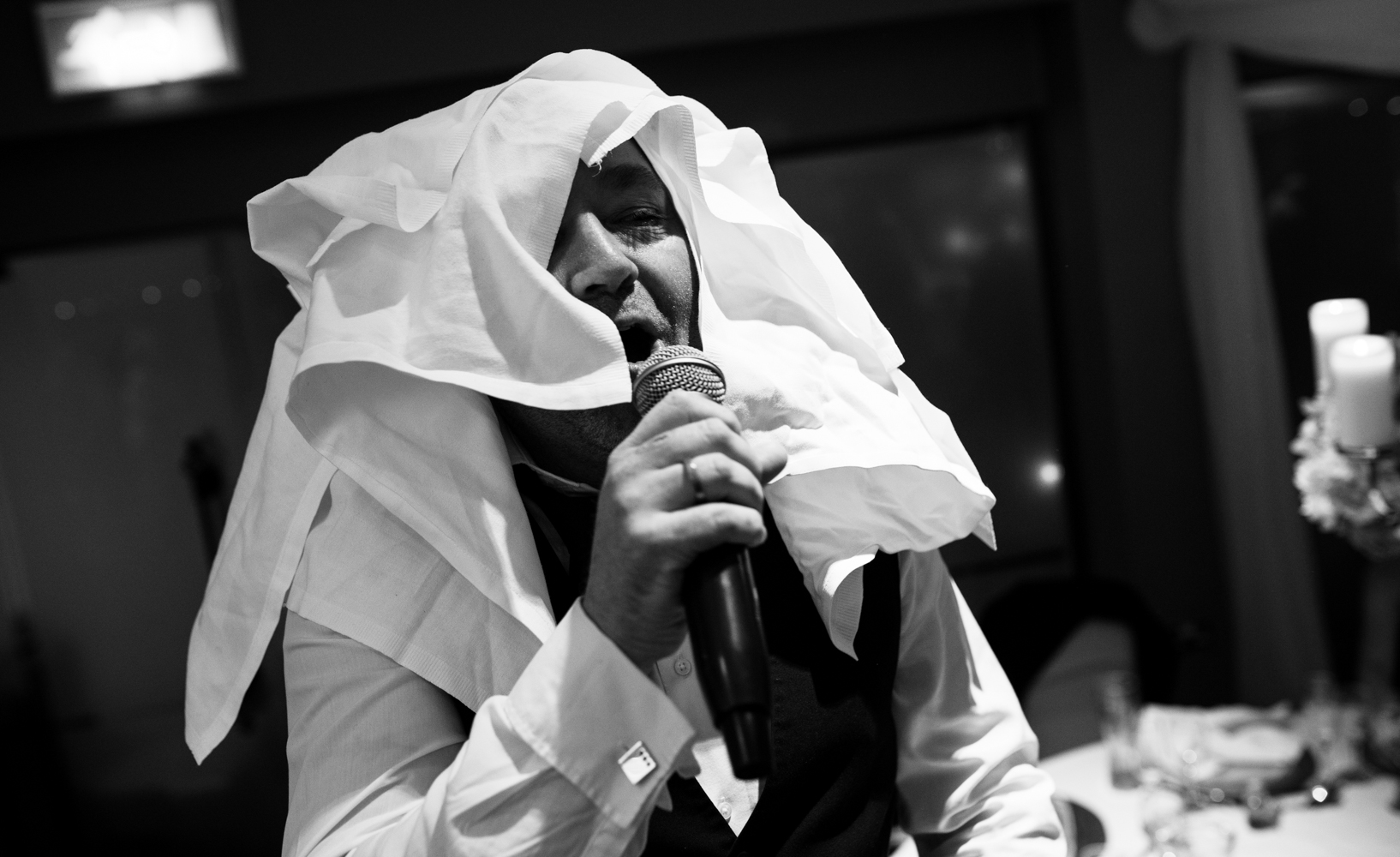 Black and white images of one of singing waiters with his head covered in table napkins