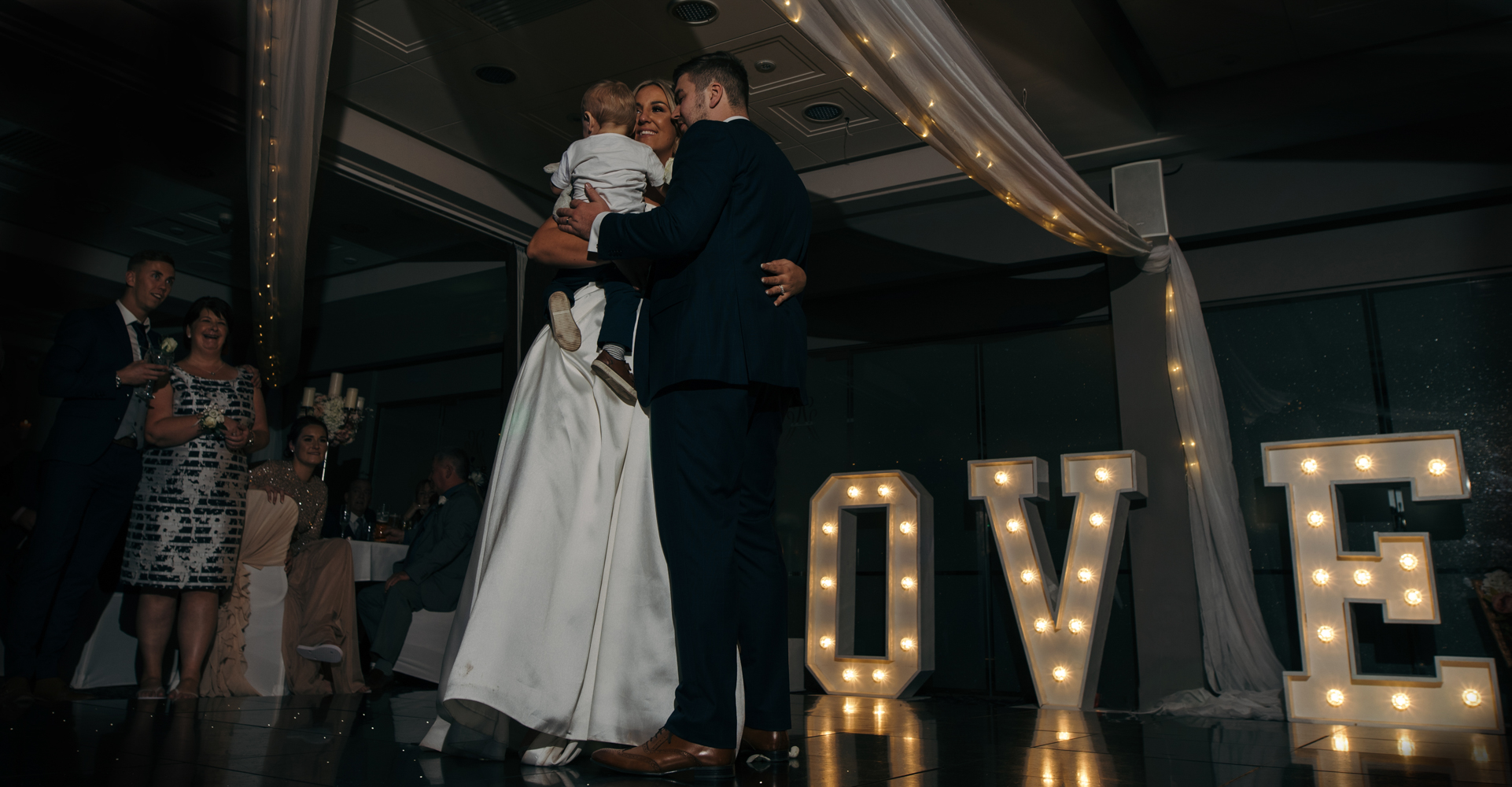 The bride and groom during the first dance with their little boy