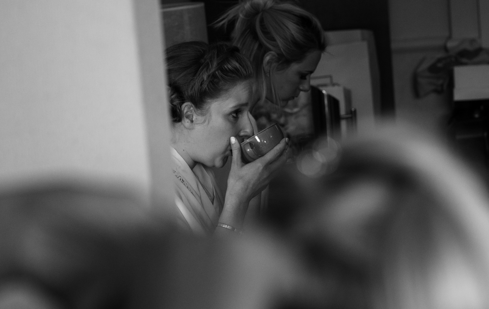 Black and white photo of a bridesmaid enjoying a nice cup of tea during morning preparations