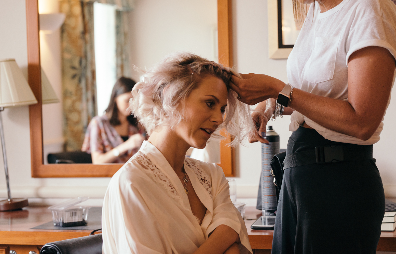 A bridesmaid having her hair done during morning preparations