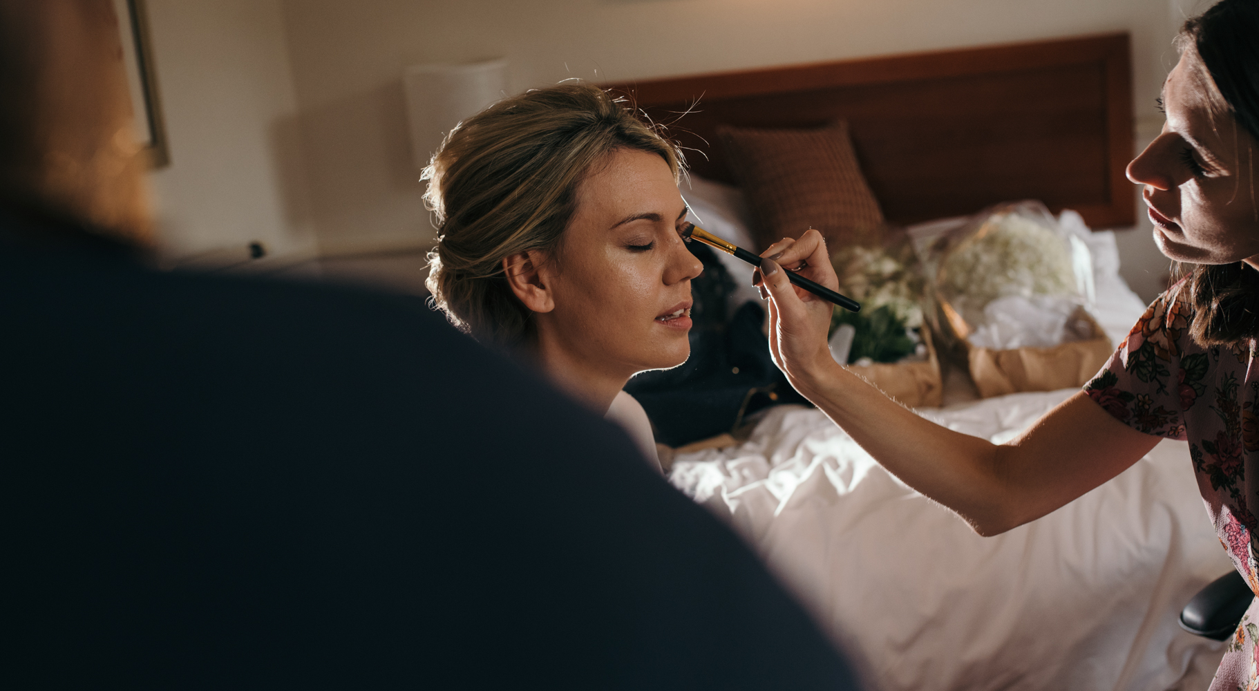 The bride having makeup and hair done during morning preparations