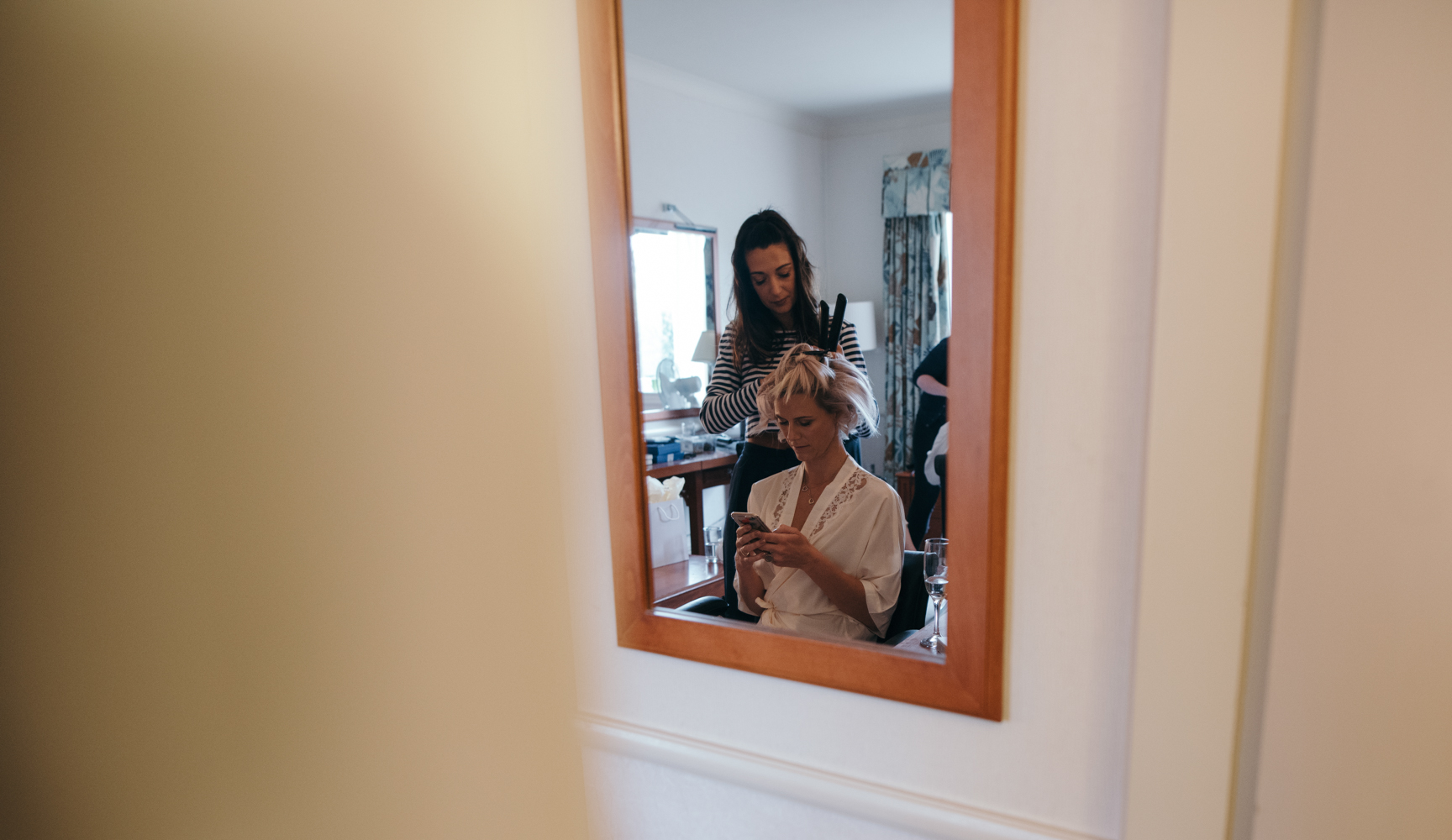 A bridesmaids reflection in a mirror during morning bridal preparations