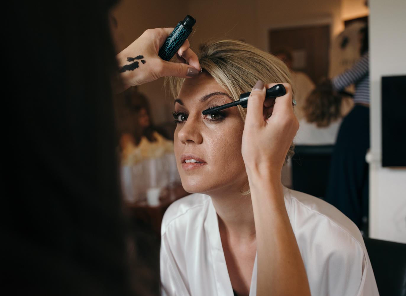 The bride having her eye makeup applied.