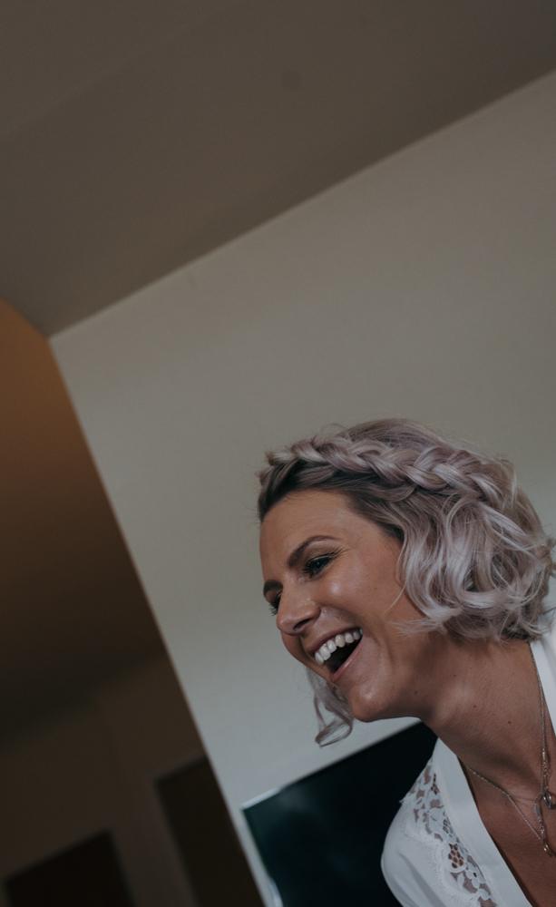 A wacky angle photo of a bridesmaid laughing
