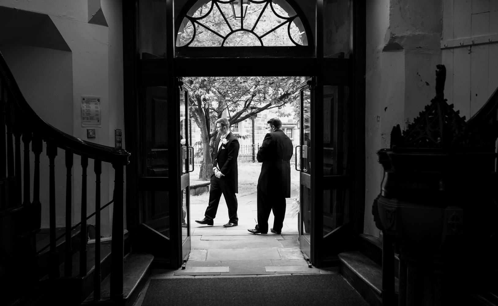 A black and white photo of the groom and his best man welcoming family and guests into the church before the ceremony