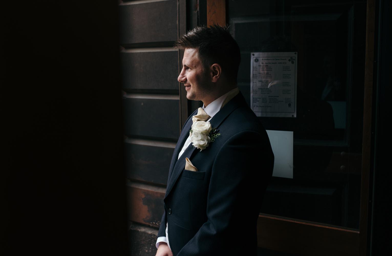 The groom solo portrait standing in the church doorway