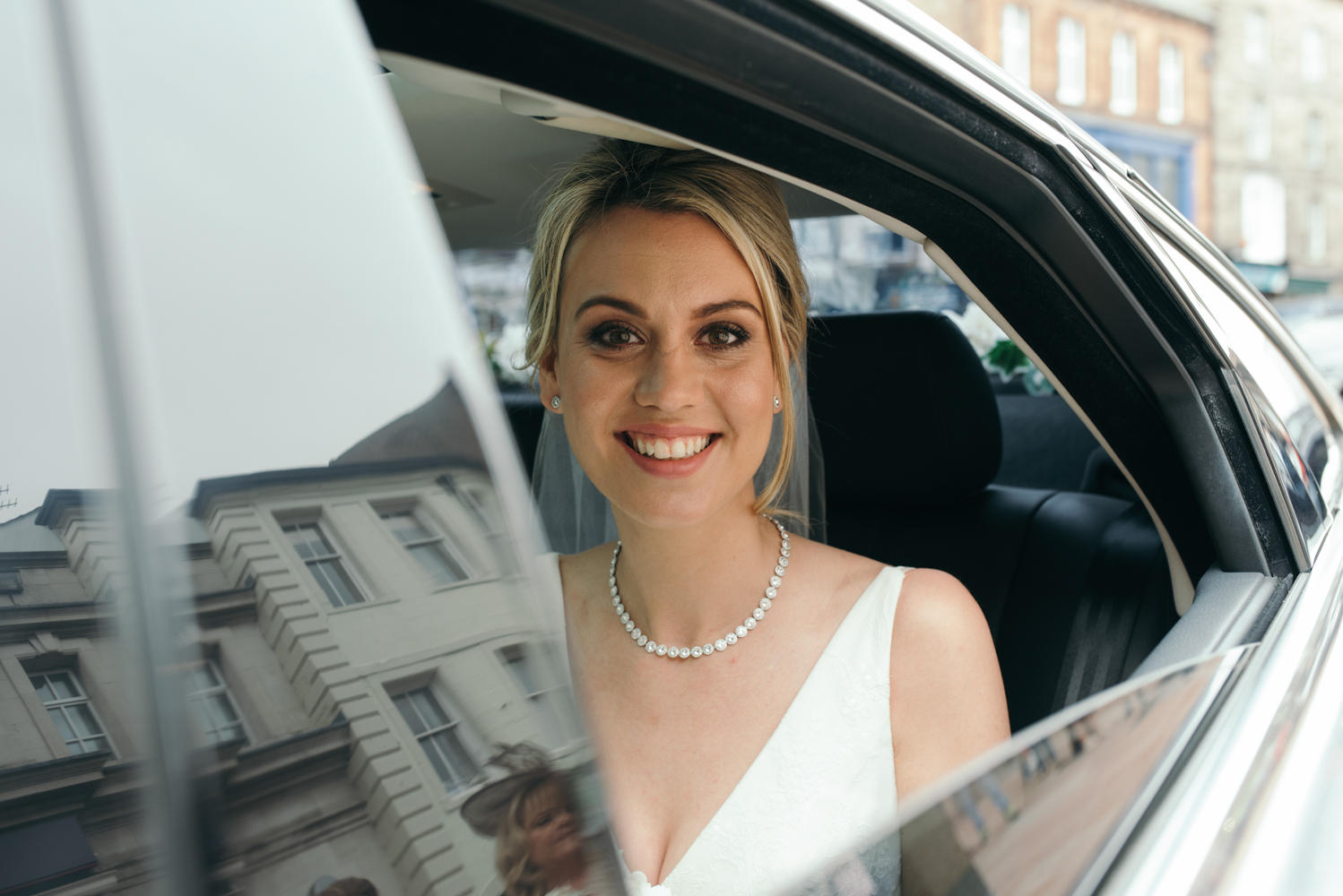 The bride sitting in the back seat of the Rolls Royce outside of the church
