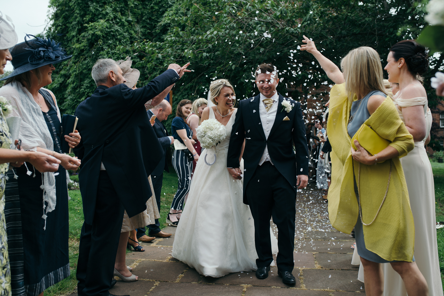 The bride and groom walking through the confetti shower