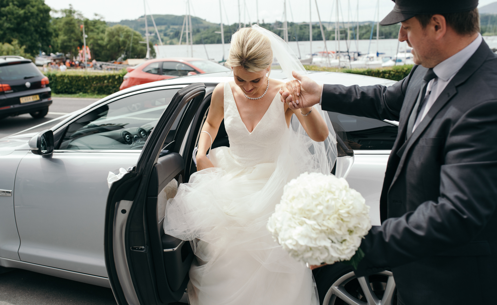The bride getting out of the car at Low Wood Bay Hotel