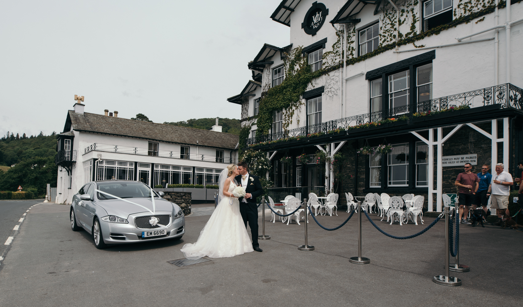 The bride and groom standing with the car outside of Low Wood Bay Hotel