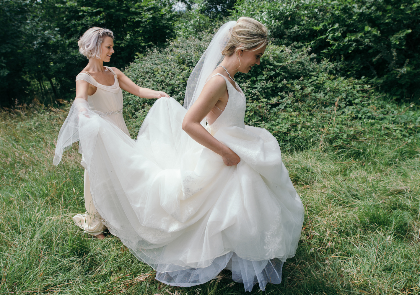 A bridesmaid helping the bride with her wedding dress during the couples portrait shoot