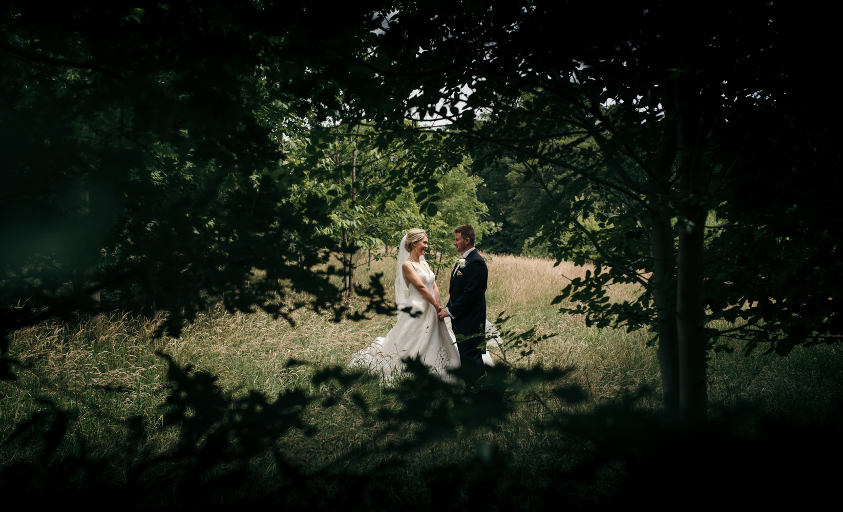 The bride and groom standing in a field during the couples portrait photo shoot