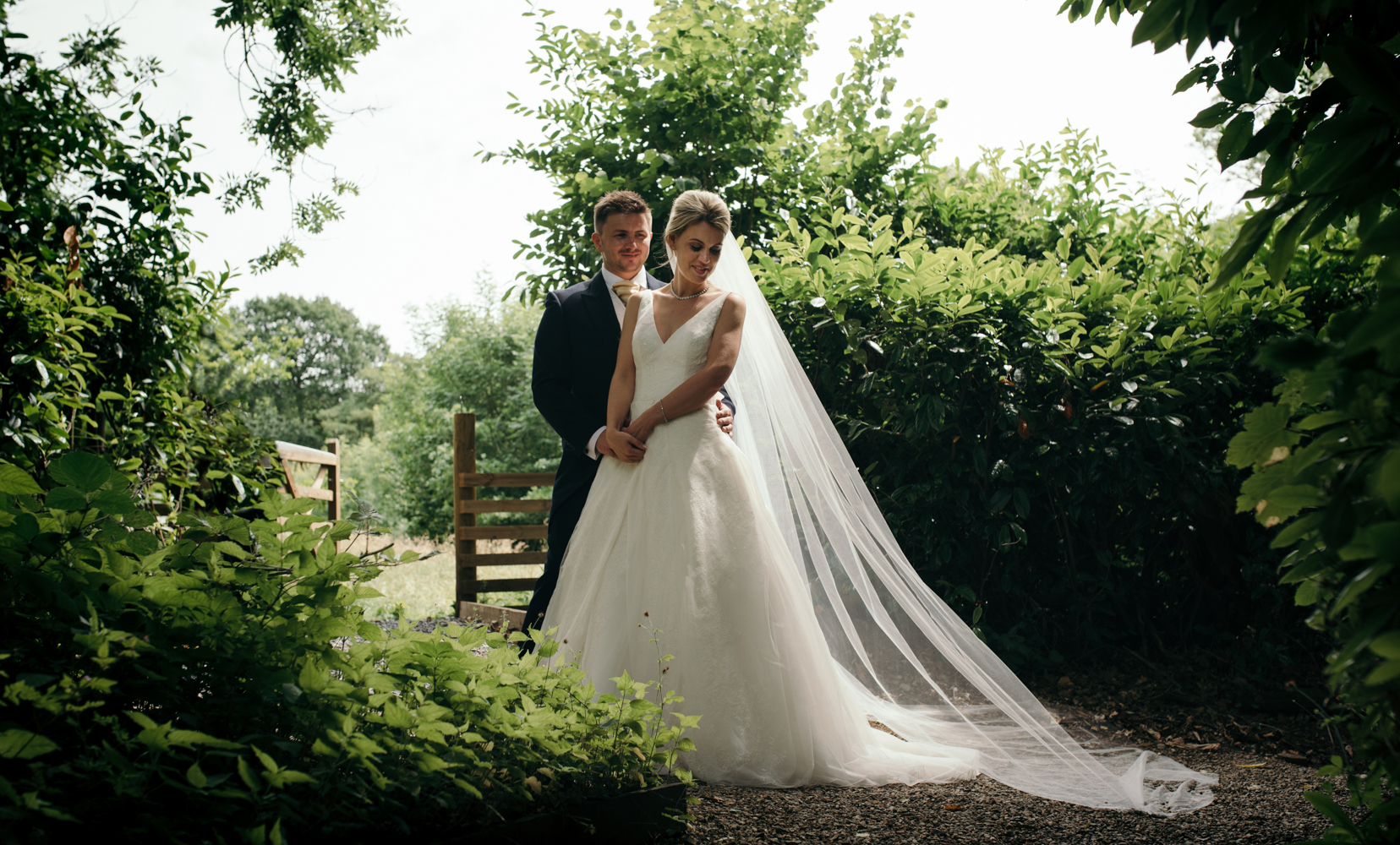 The bride and grooms portrait taken just outside the gate leading into a field