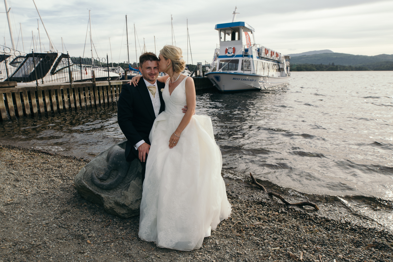 The bride and groom sitting on a commemorative stone by the jetty just after the lake cruise