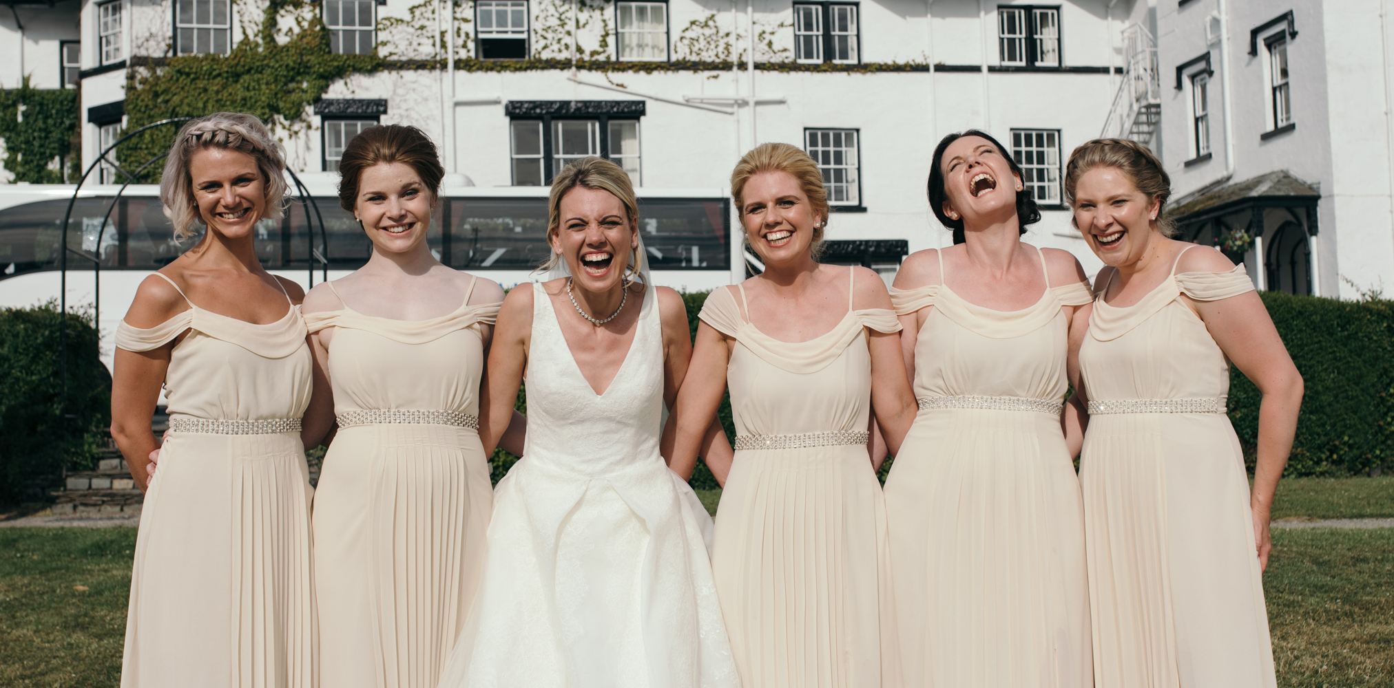 The bride and bridesmaids goofing around during the family group shots