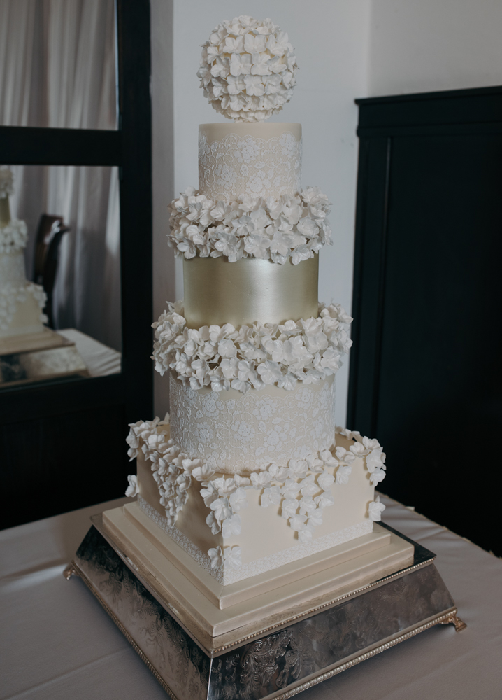 A photo of the amazing wedding cake on its stand in the wedding breakfast room