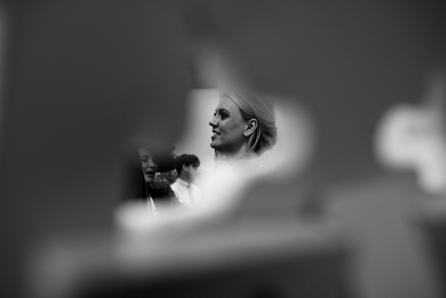 A black and white photo of the bride taken though a gap during the line up