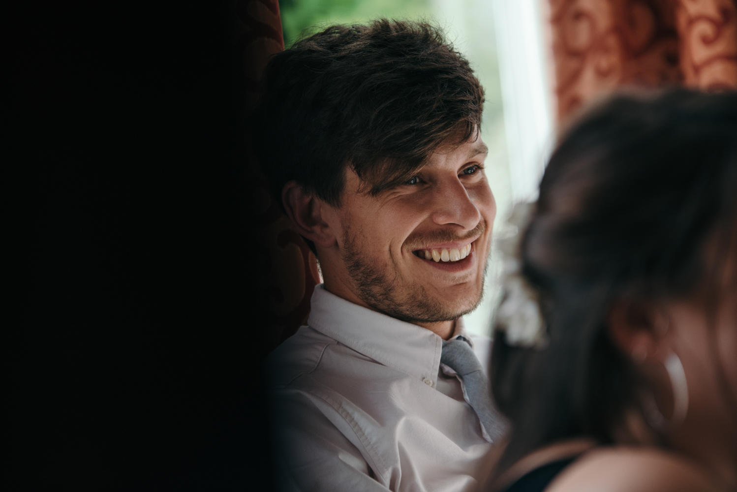 A male wedding guest having a laugh at something the groom said in his speech