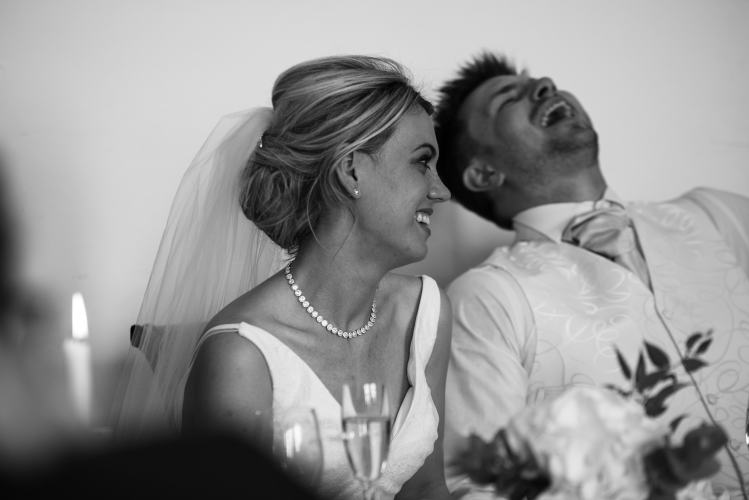 the bride and groom laughing during the best mans speech