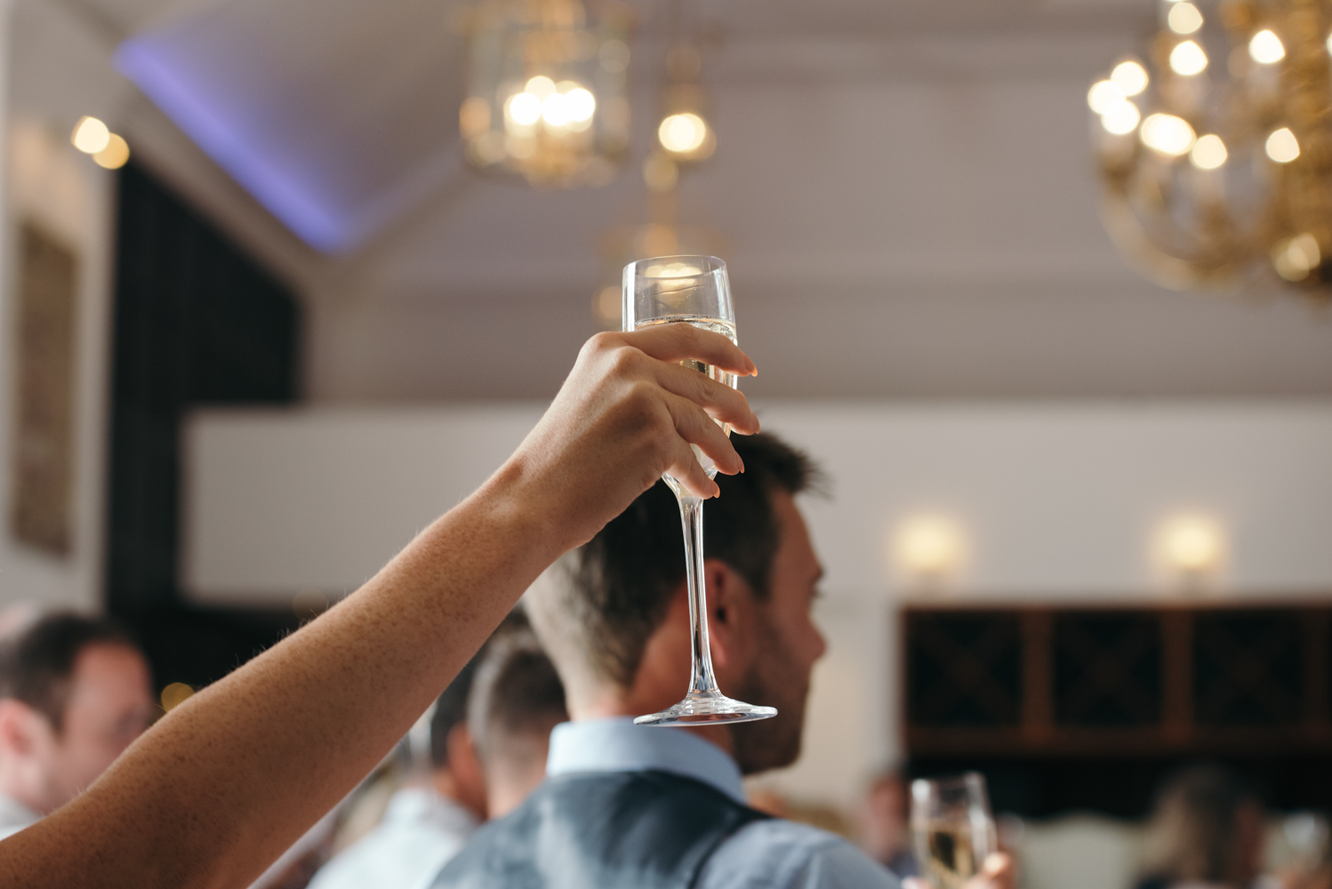 A guest holds up a champagne glass at the end of the speeches