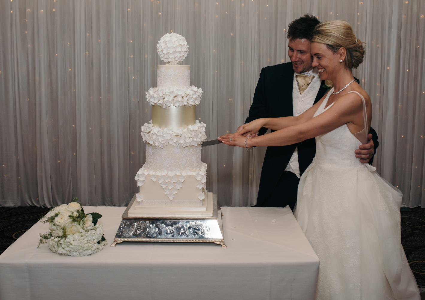 The bride and groom cutting the wedding cake