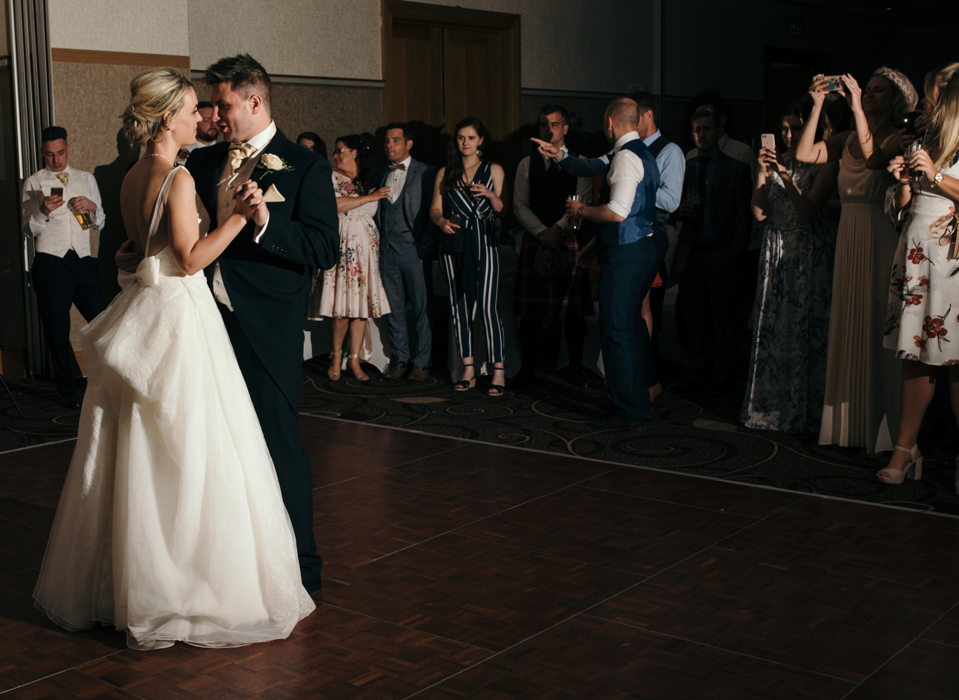 The bride and groom during the first dance with all of the guests standing watching