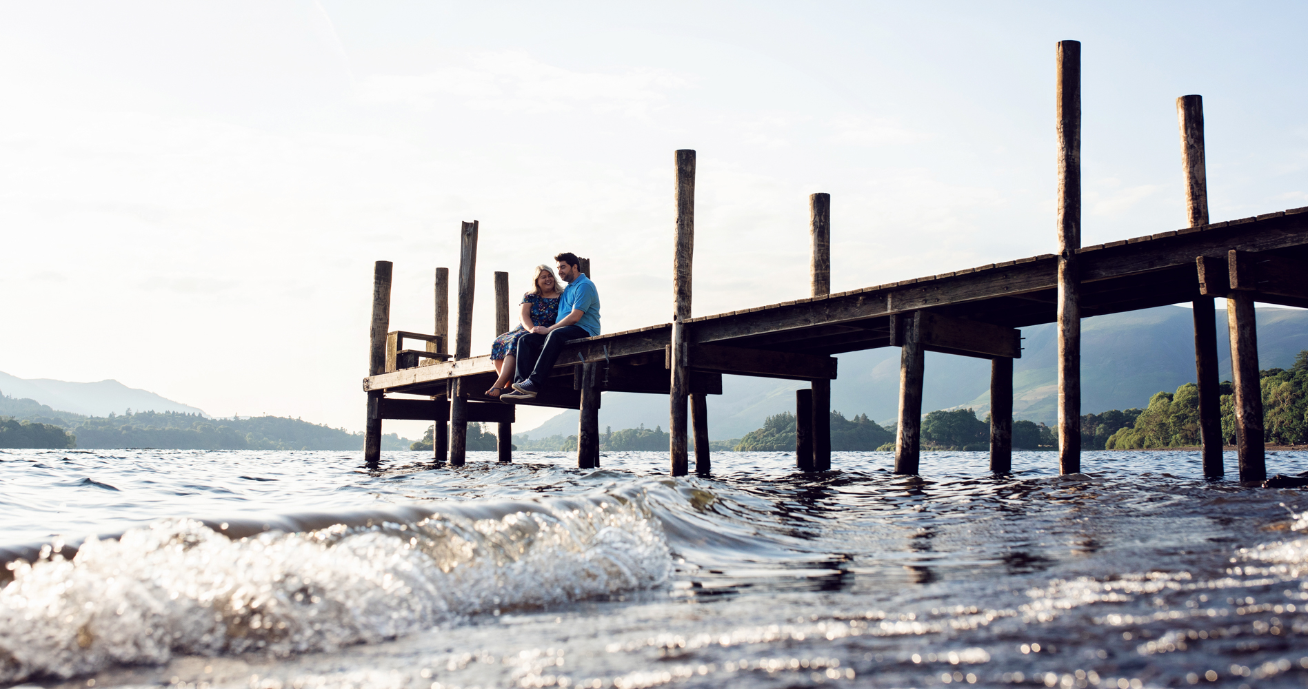 Pre shoot - A couple sitting on the pier at Ashness Bridge on the shores of Derwent water in the Lake District