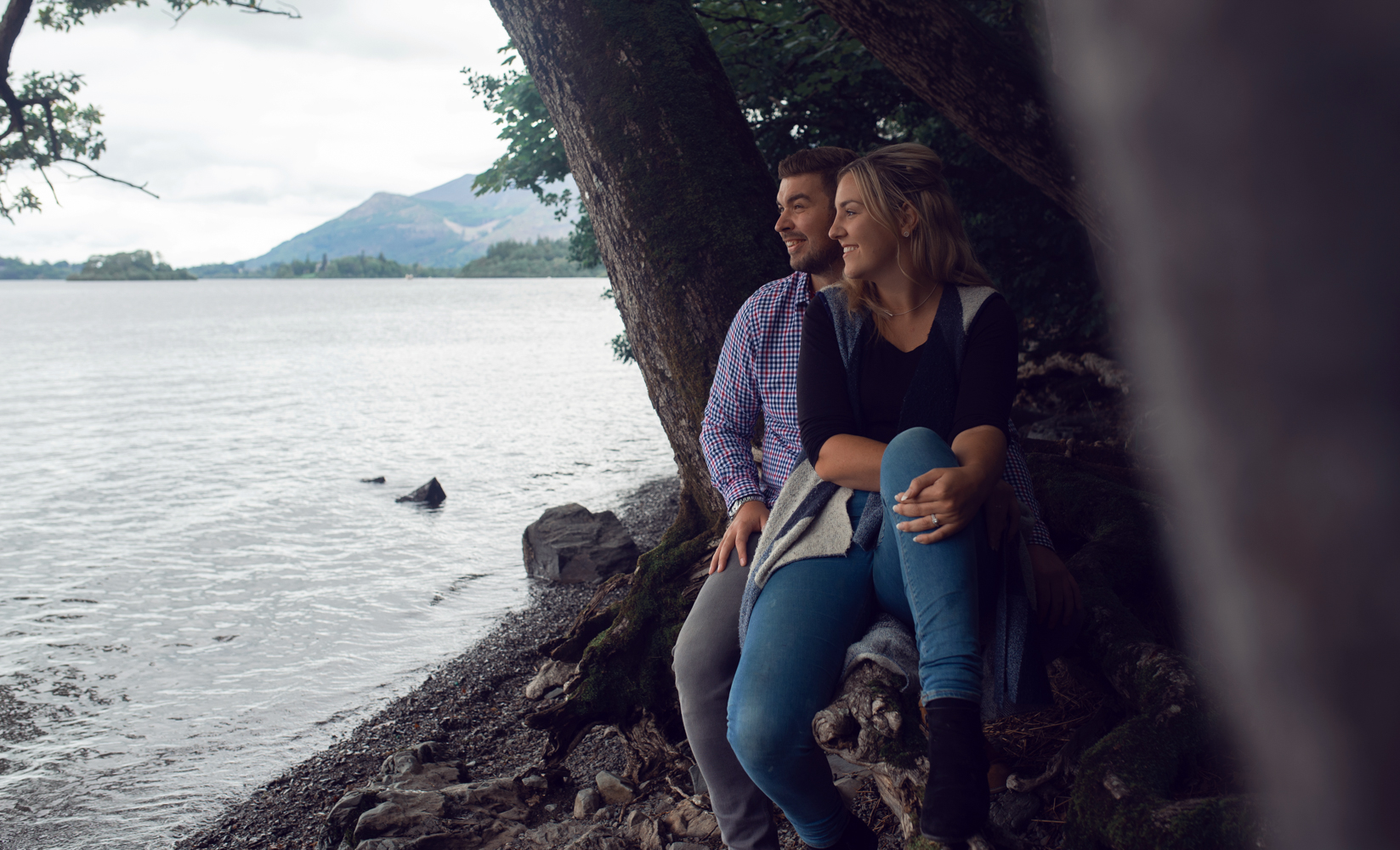 Pre shoot - A couple sitting on a fallen log on the shores of Derwent water in the Lake District