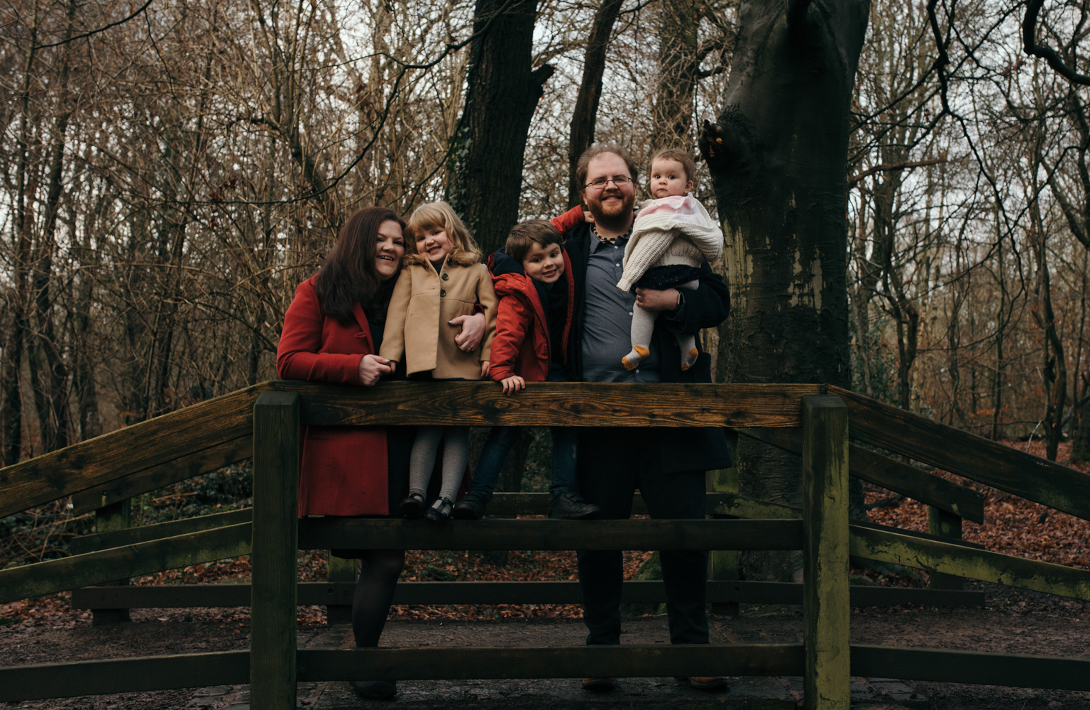 Another family group photograph standing on a bridge in the woods