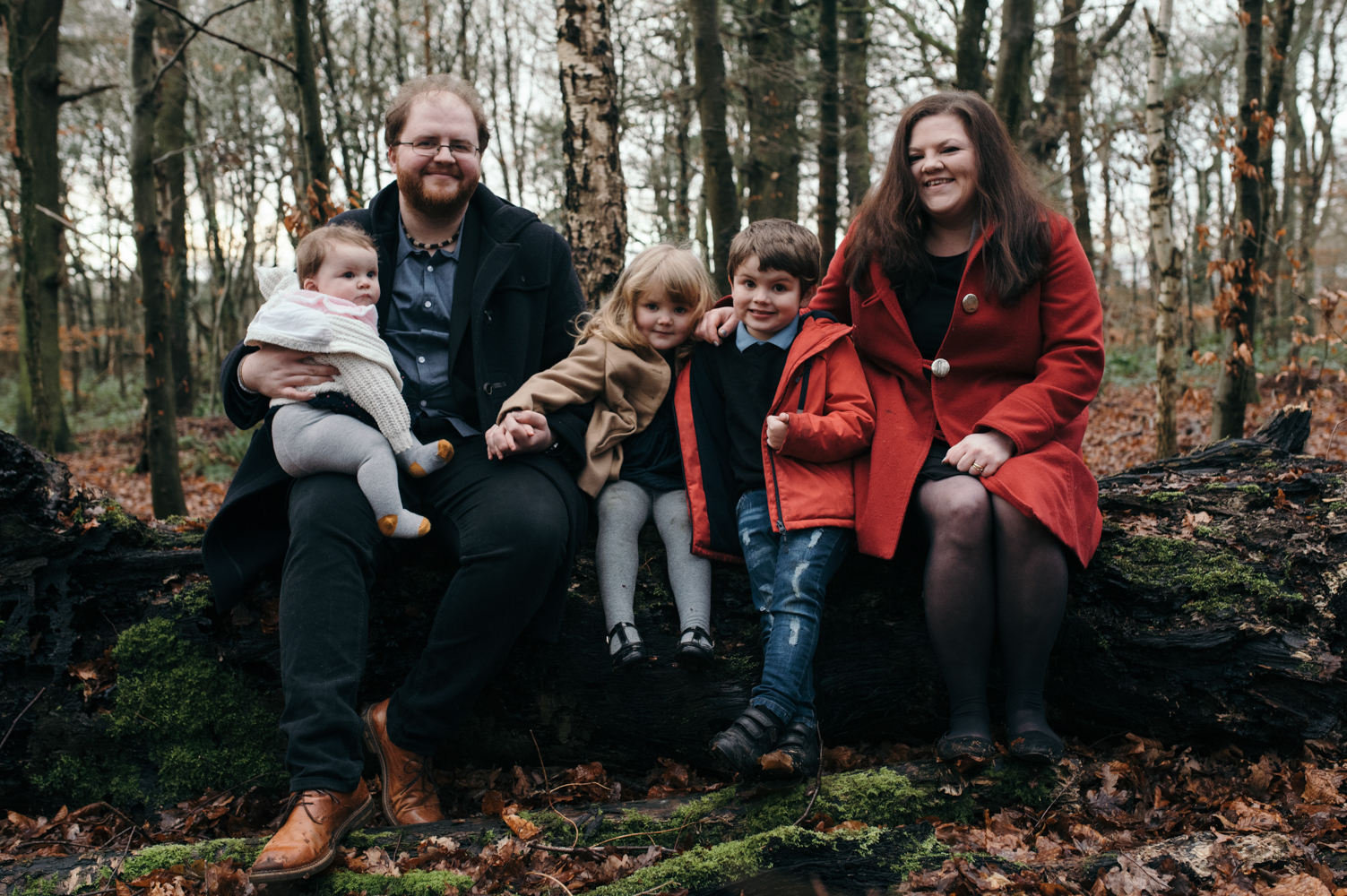 A family group photo sitting on an upturned log in the woods