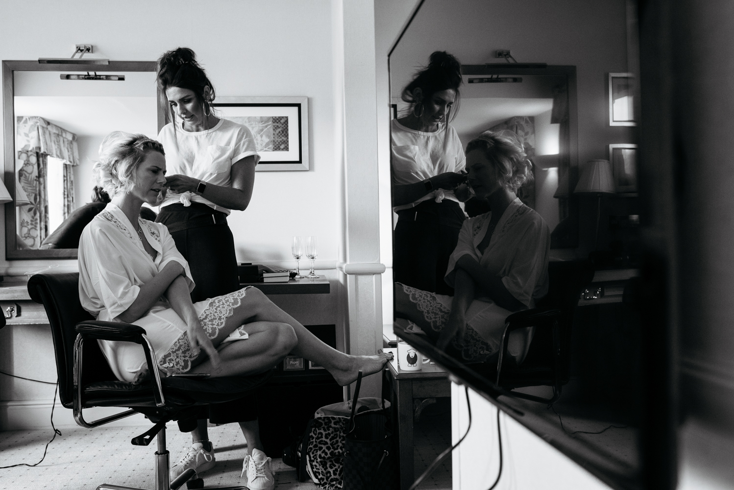 A black and white photograph of a bridesmaid having her hair done during morning bridal preparations