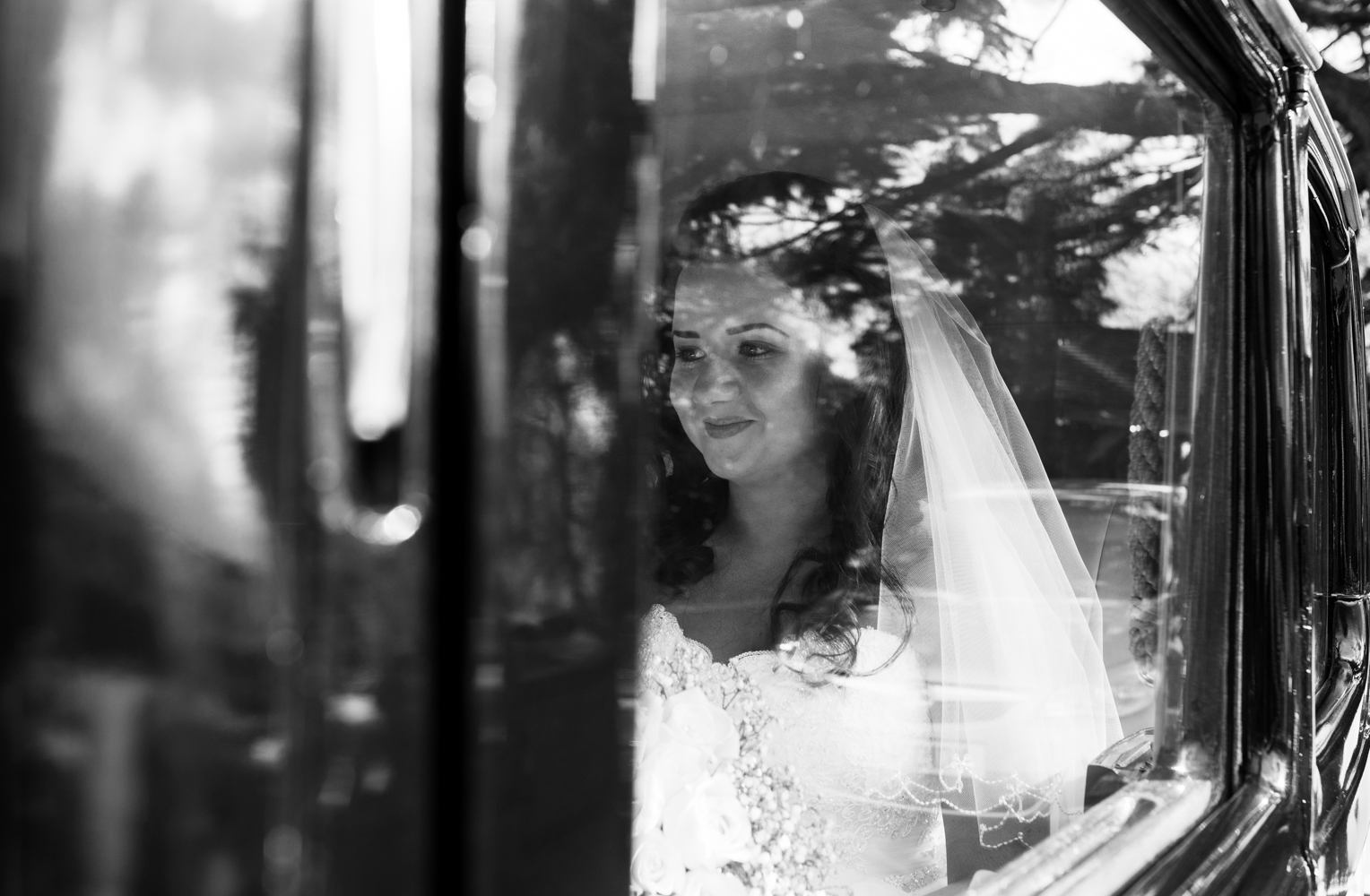 A black and white photograph of the bride sitting in the car prior to her wedding ceremony