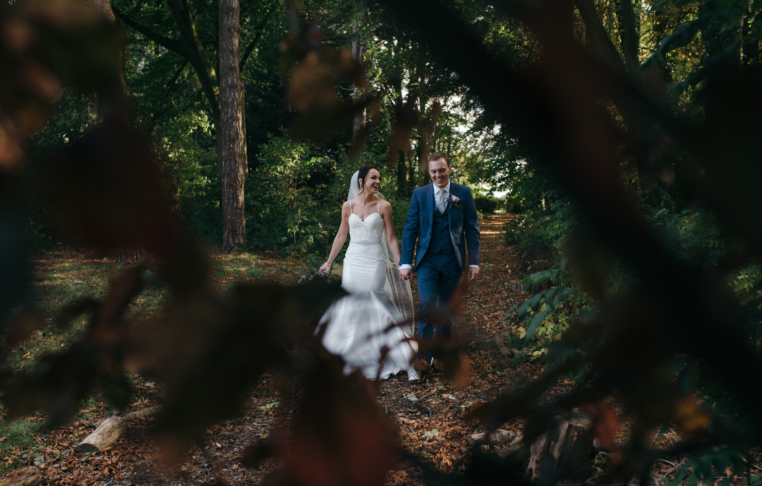 The bride and groom walking through the woods