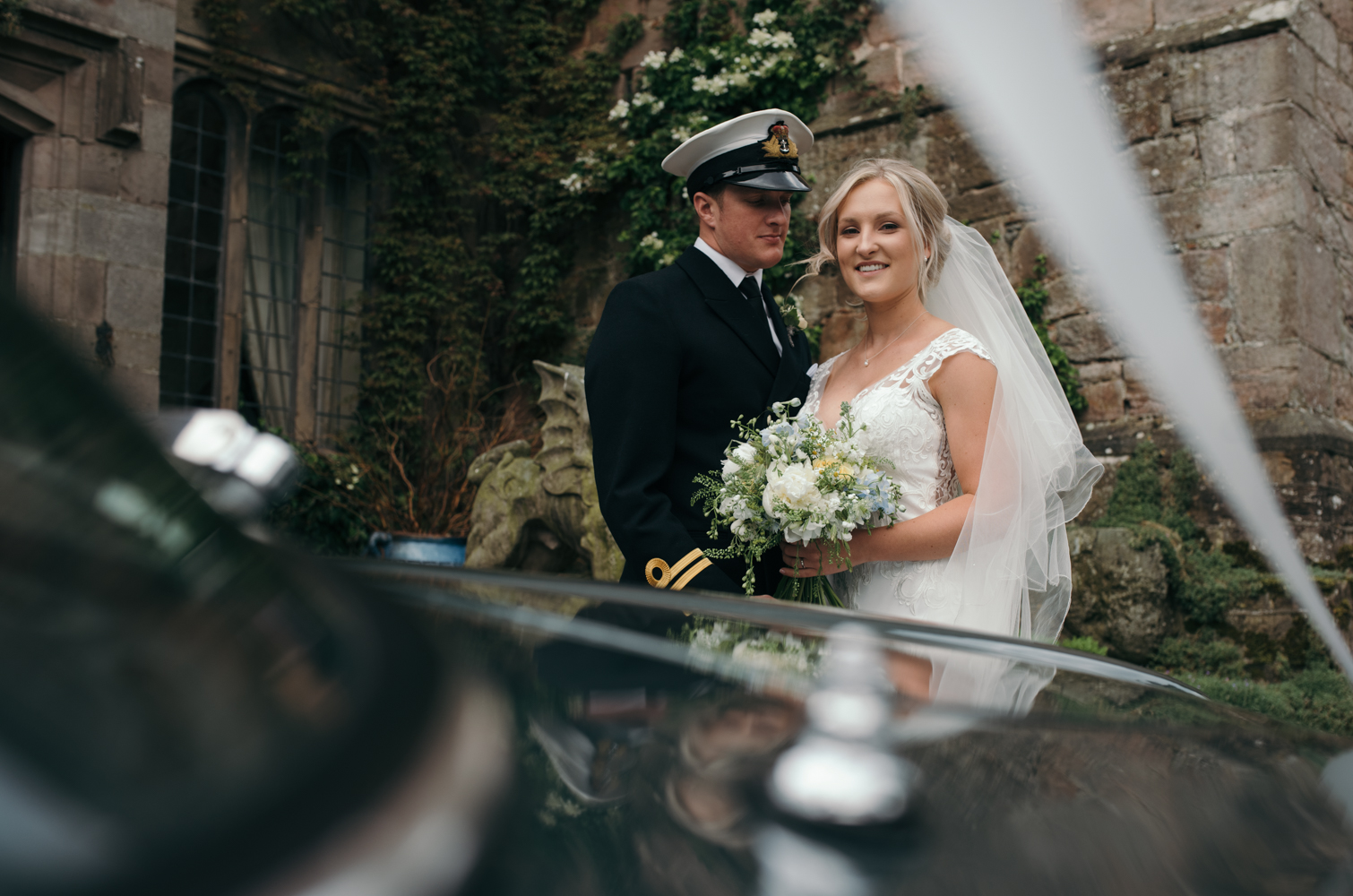 The bride and groom reflected in the bonnet of the aston martin car