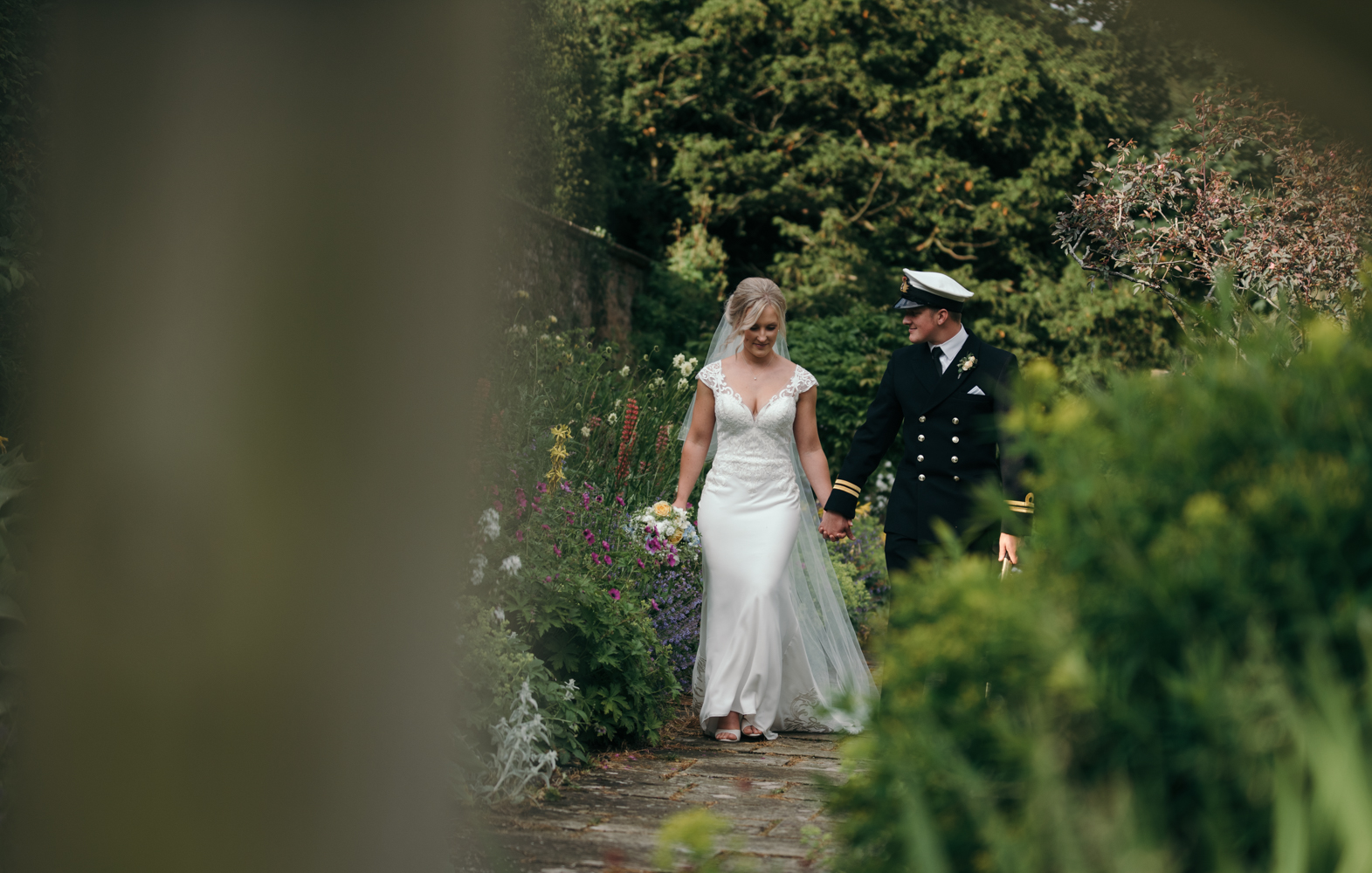 The bride and groom walking in the secret garden