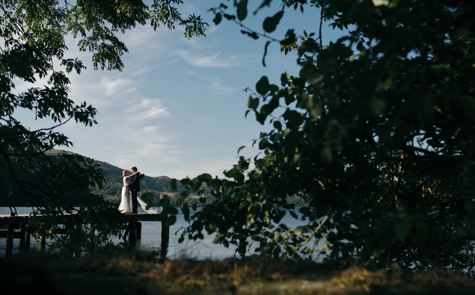 A bride and groom standing on a jetty Ullswater Lake District