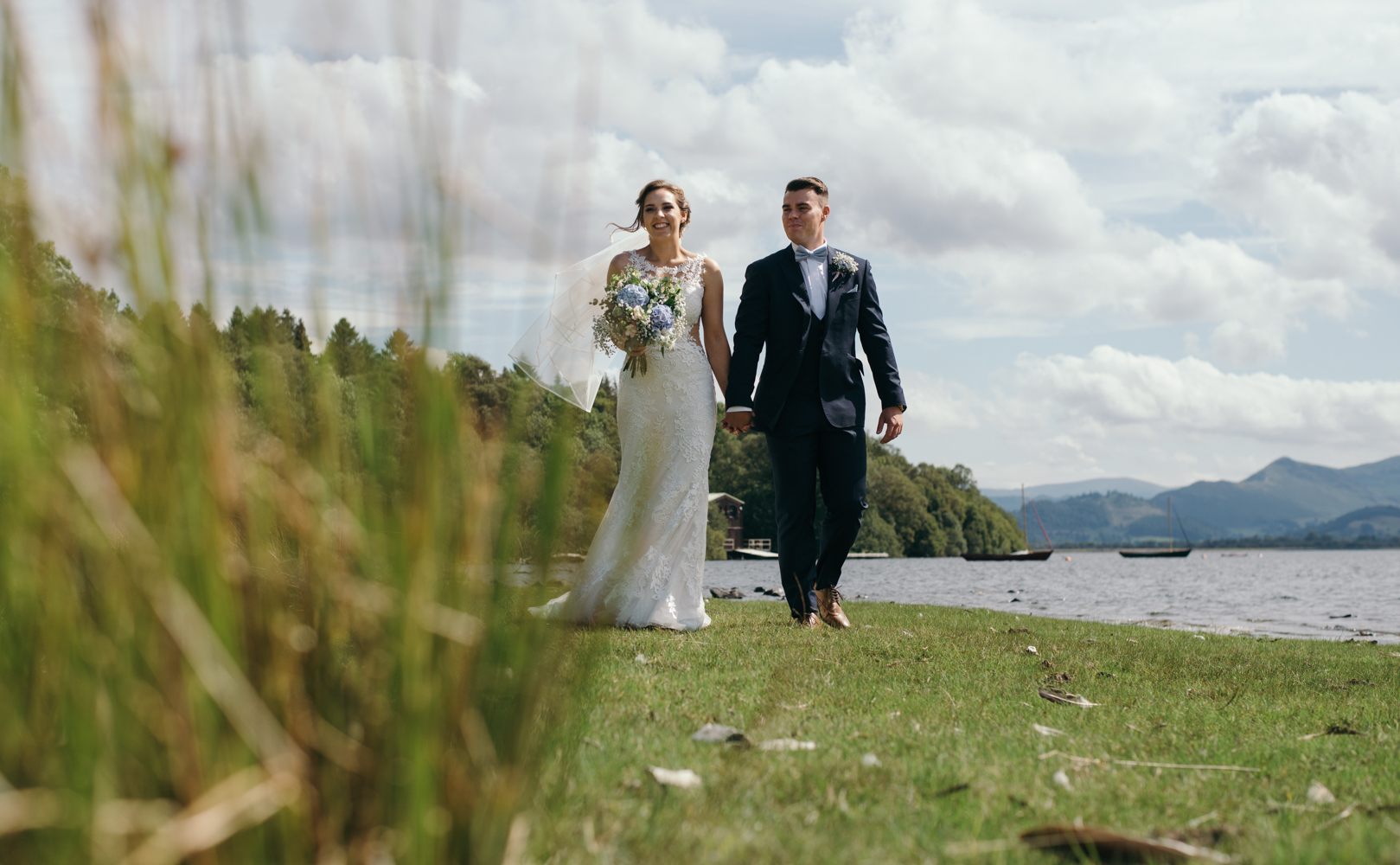 A bride and groom walking along the lake side