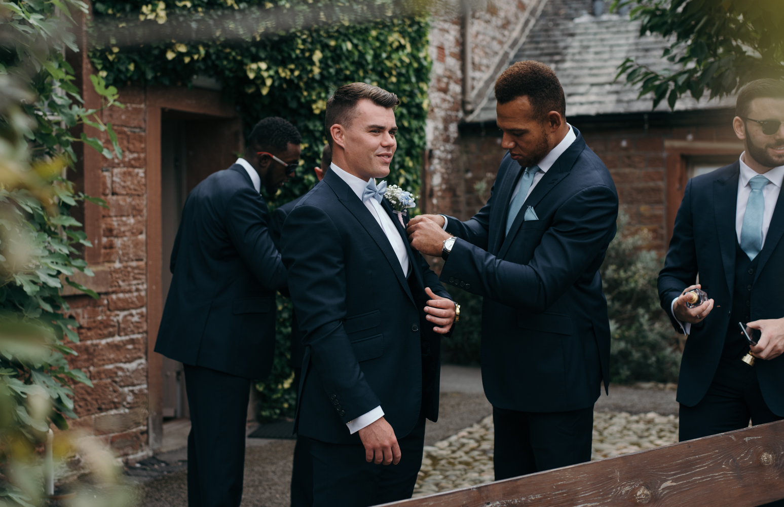 A groom getting some help with his button hole