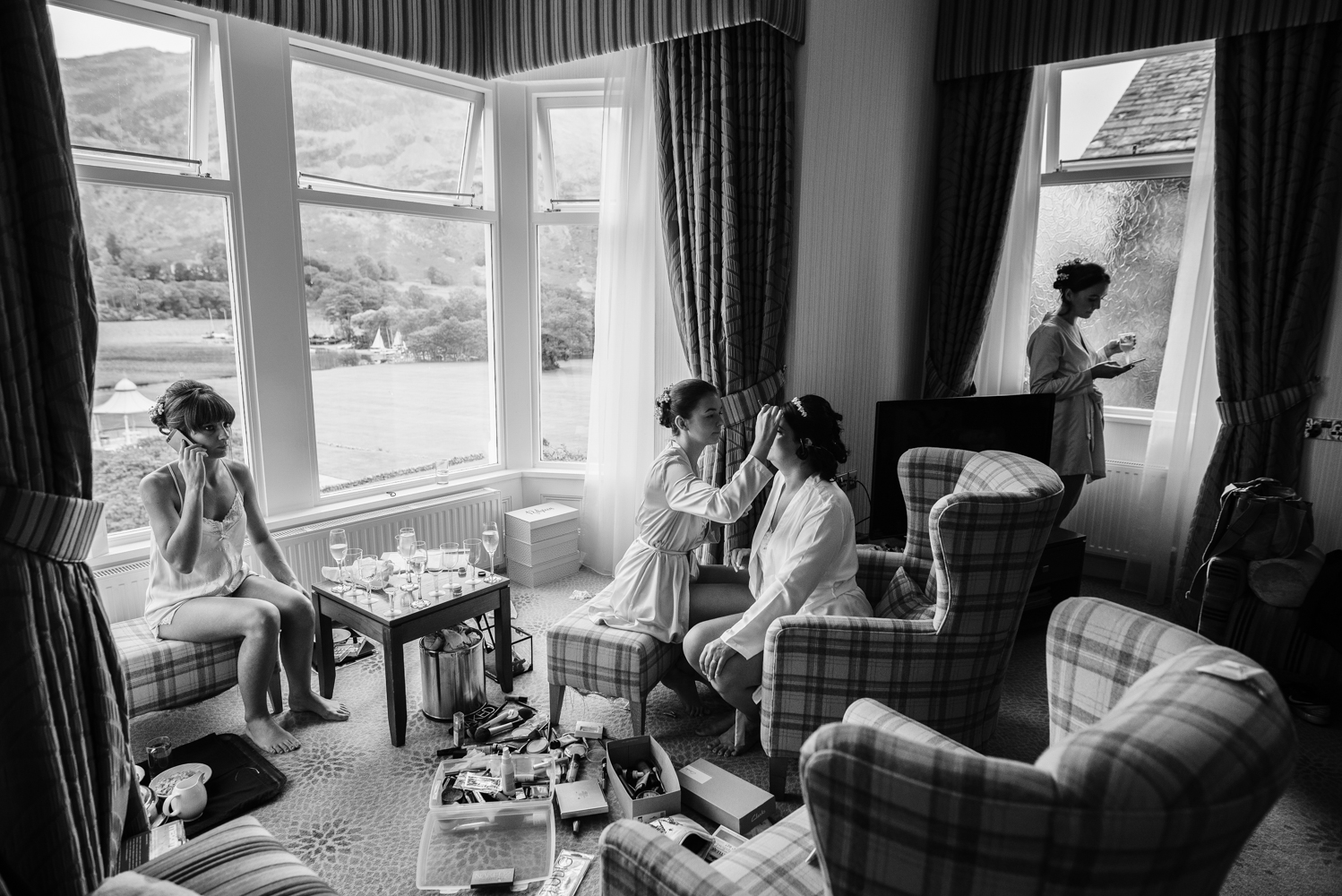 Black and white wide angle photo of bridal preparations with the lake district mountains in the background
