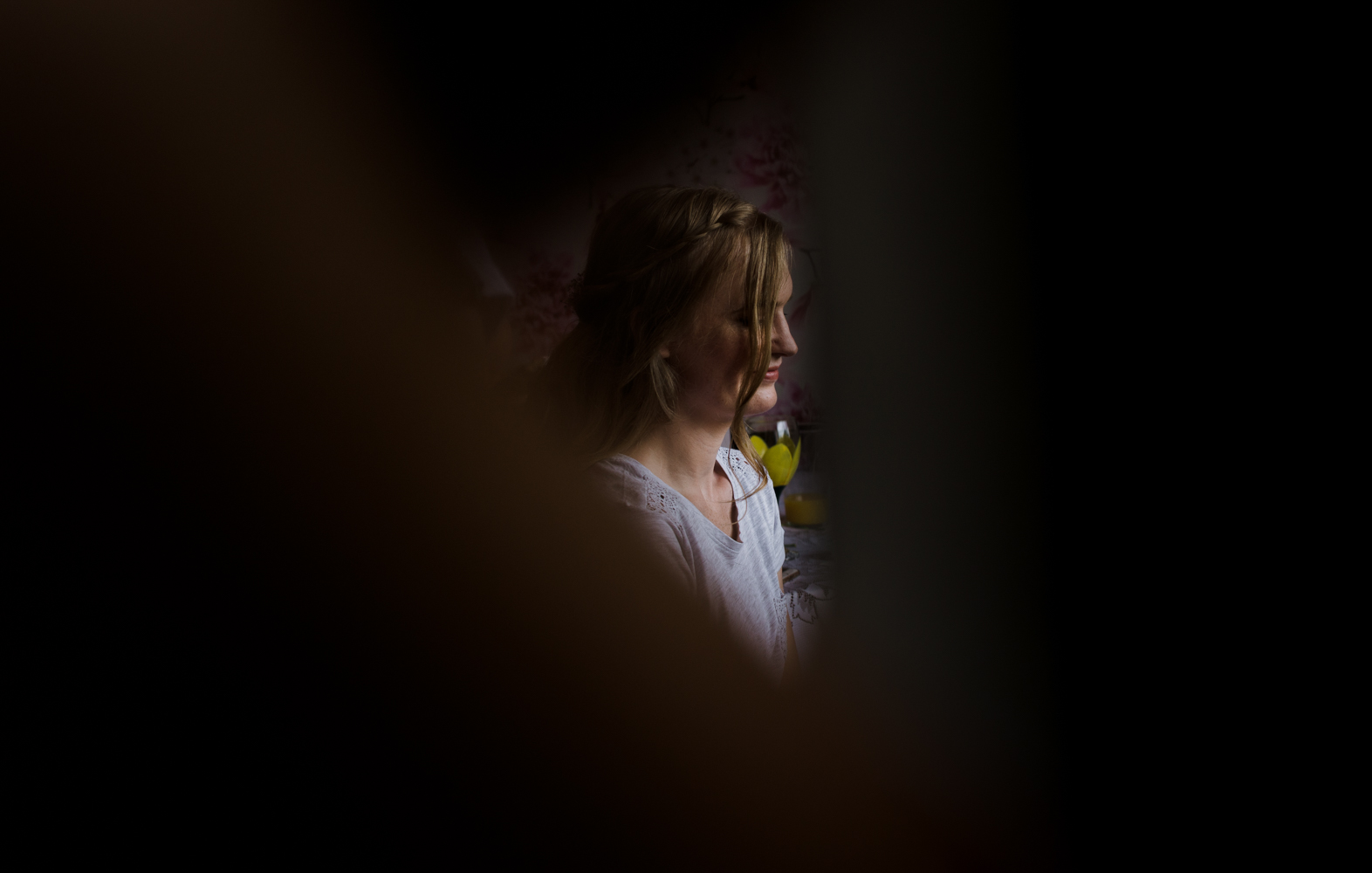 A moody photo of one of the bridesmaids during preparations