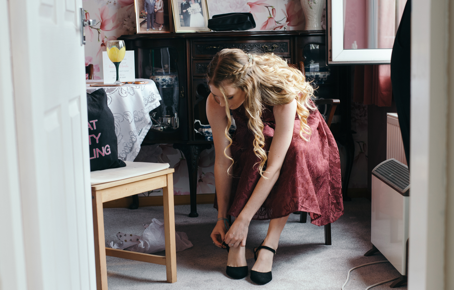 A bridesmaid putting her shoes on
