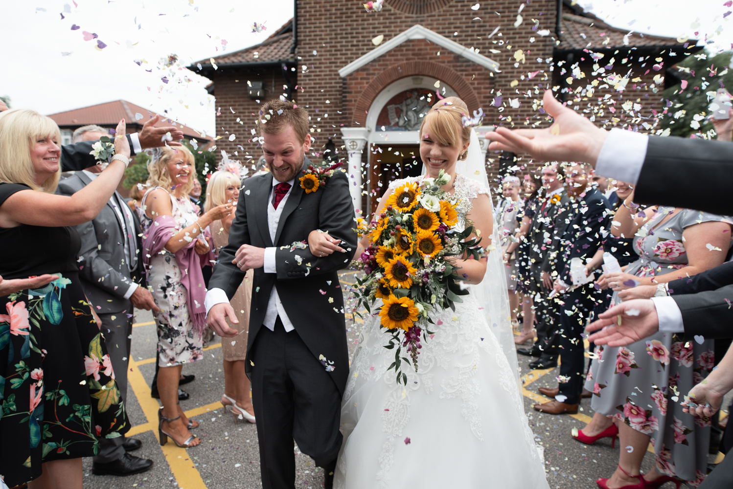 The bride and groom in an avalanche of confetti