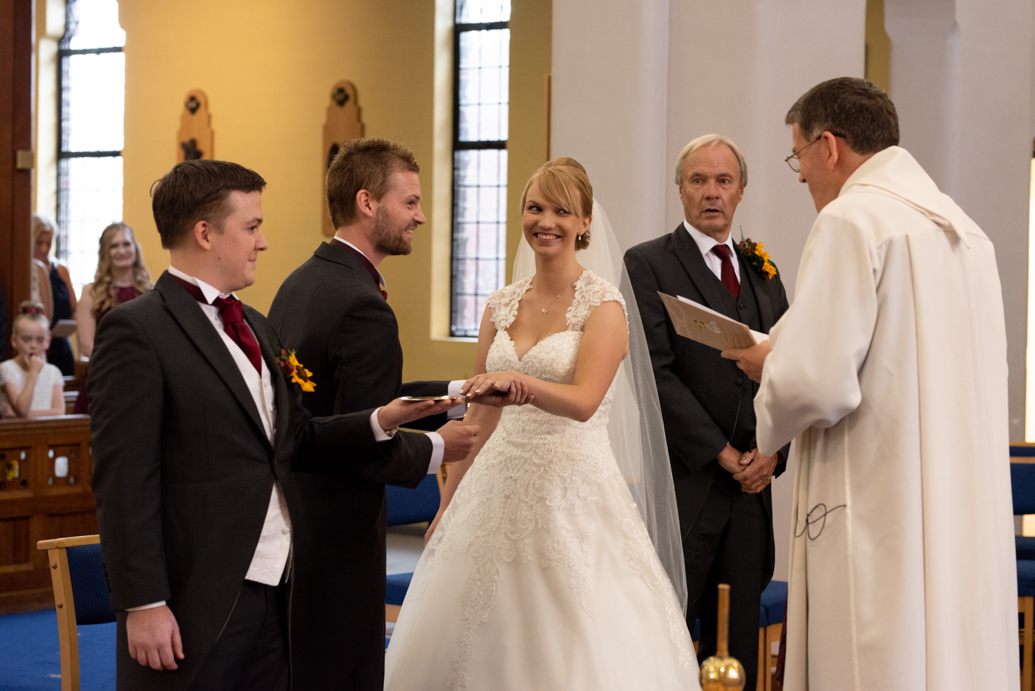 The bride and groom have a laugh during the exchange of wedding rings