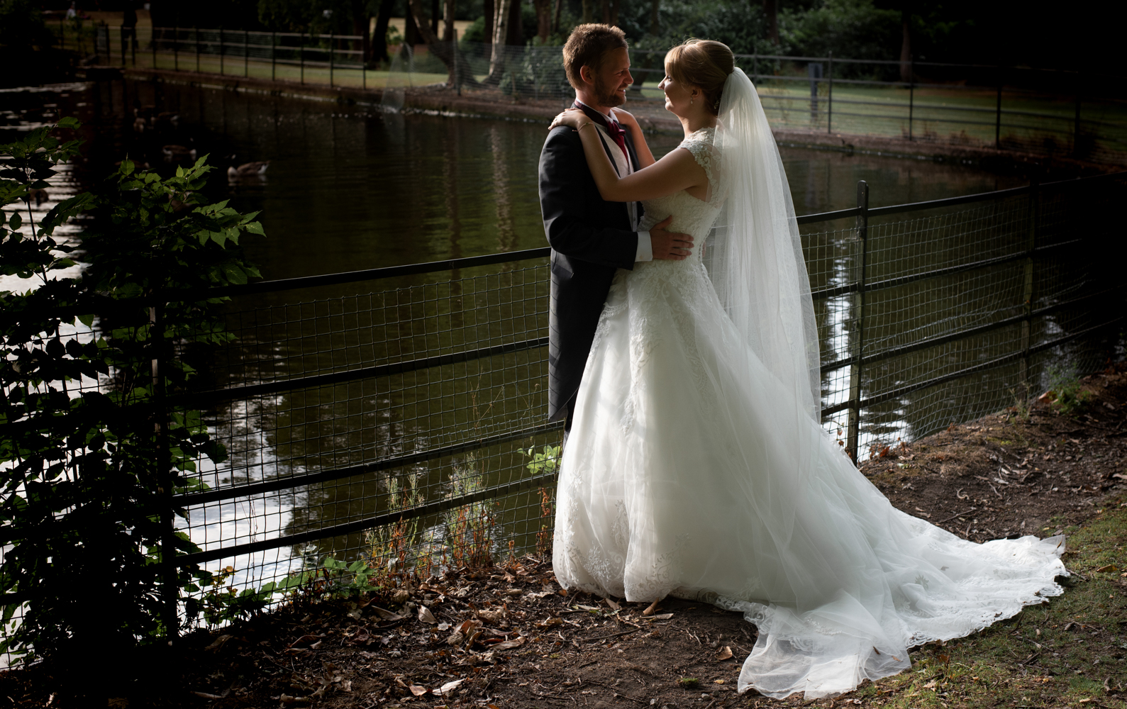 Another photo of the bride and groom standing by the lake in the early evening sunlight